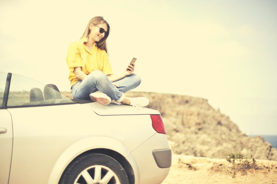 Girl sitting on car checking phone